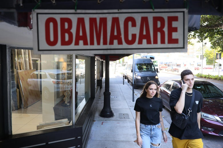 Two young people walk past an Obamacare sign hanging outside a storefront in Miami