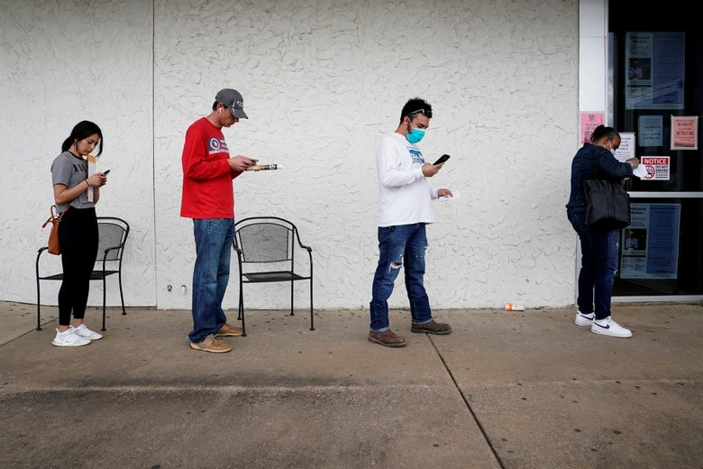 Four Americans wait in a socially distanced line to collect unemployment benefits.