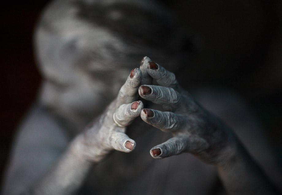 The ash-encrusted hands of a sadhu (Hindu holy man) are seen as he sits beside a fire after applying ashes to his face and body at his ashram at Pashupatinath Temple in Kathmandu, Nepal, March 4, 2013.