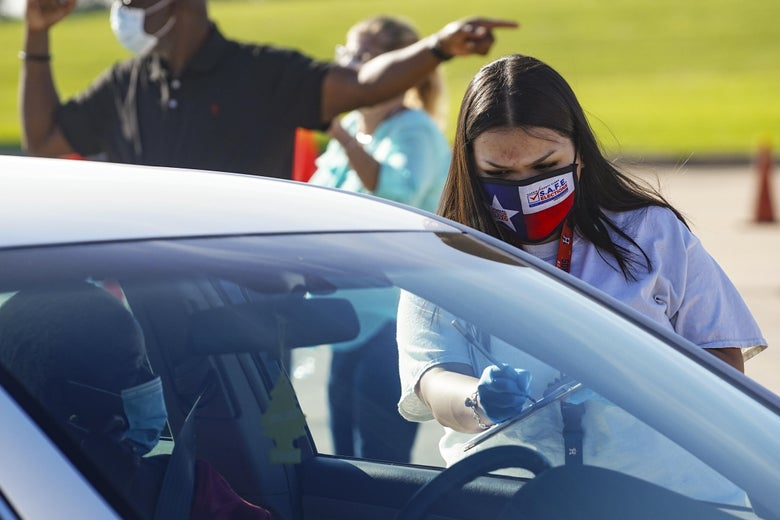 An election worker accepts mail in ballot from a voter at drive-through mail ballot drop off site at NRG Stadium on Oct. 7, 2020 in Houston, Texas.