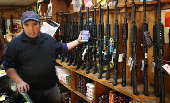 New York City Police Commissioner Ray Kelly (R) is handed a confiscated AR-15 assault rifle above a table of illegal firearms sold to undercover officers in a large weapons.