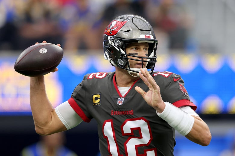 Brady in his Bucs uniform pulling the ball back to pass as he looks downfield
