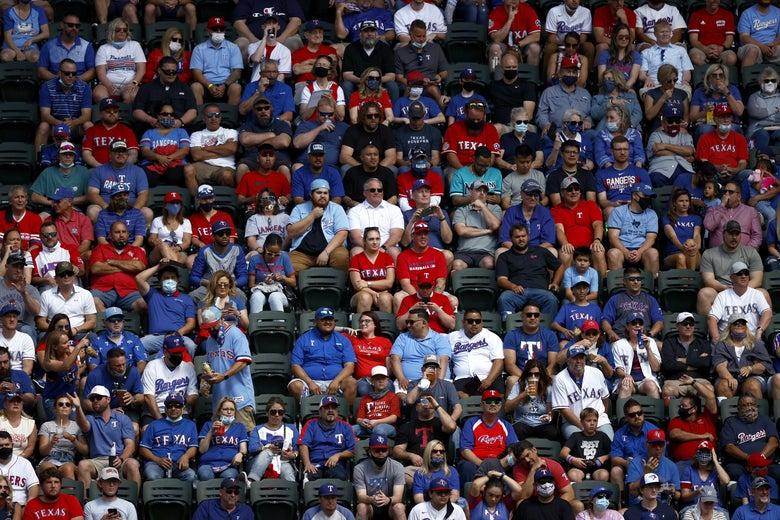 Mostly maskless fans sit shoulder to shoulder in the stands