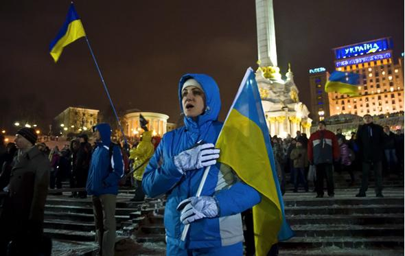 A woman sings the national anthem during a rally on Independence Square.
