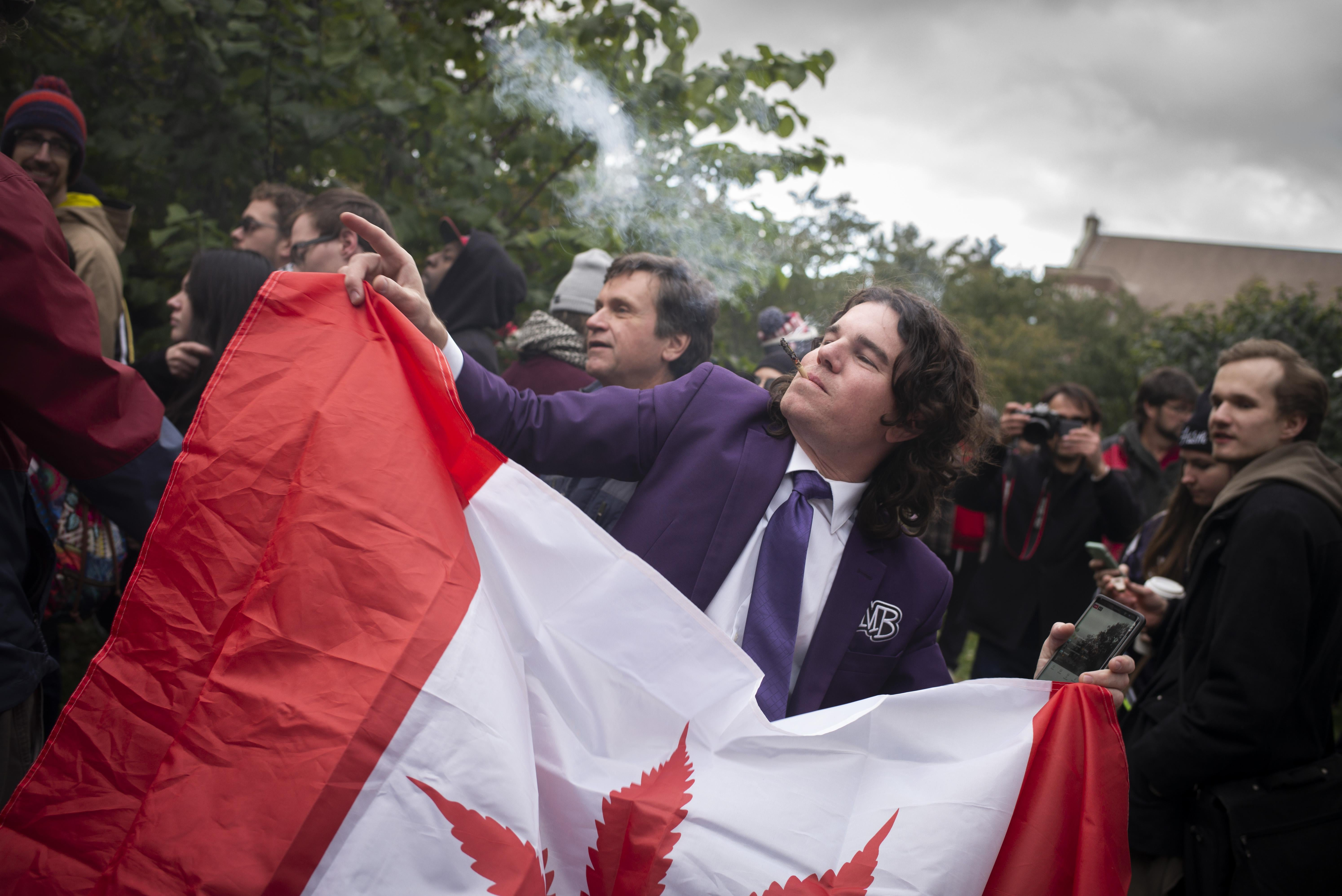 A cannabis user holds a Canadian flag.