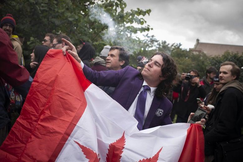 A cannabis user holds a Canadian flag.
