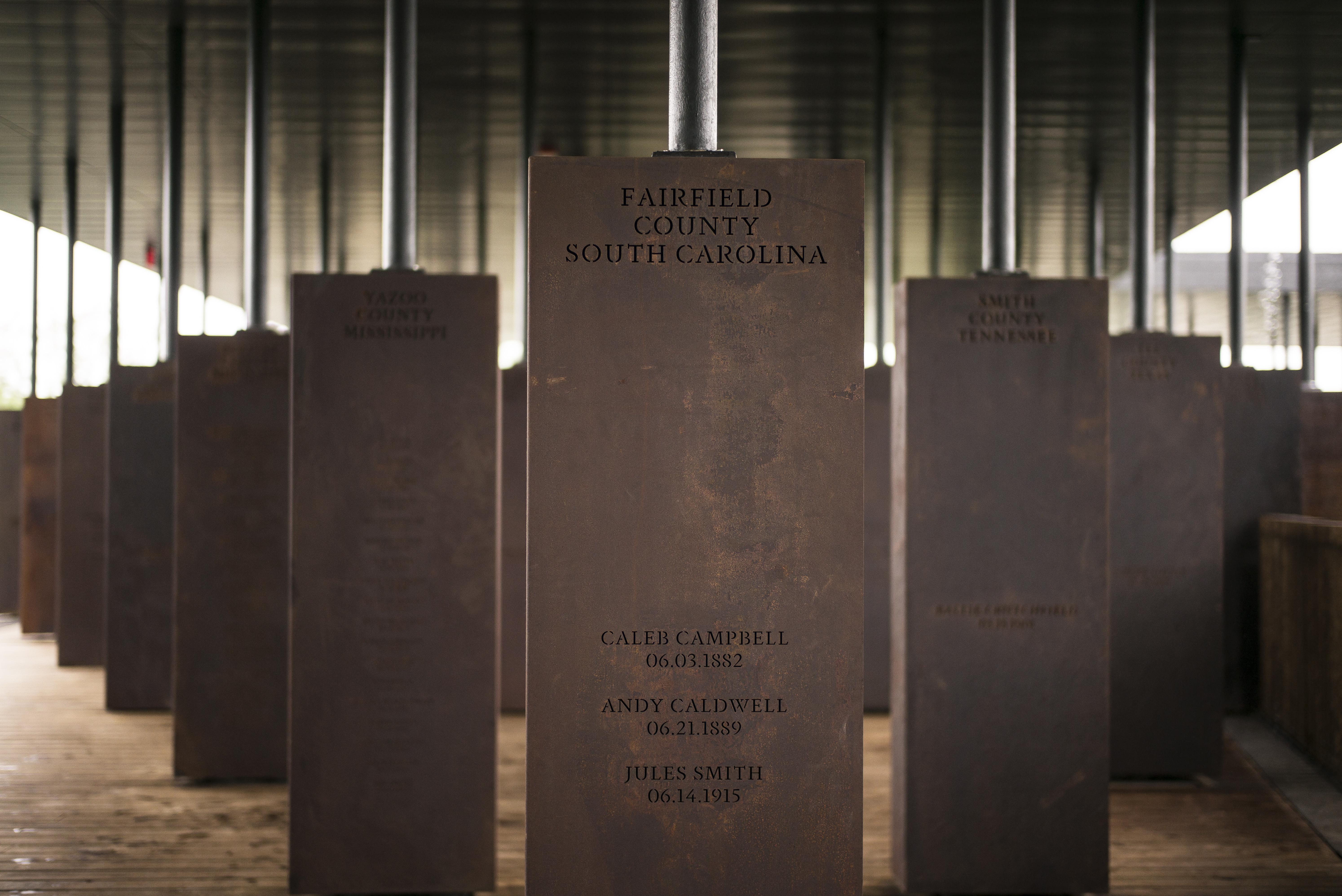 Markers held by poles connected to the ceiling of the National Memorial for Peace and Justice display locations and names on earthy brown-colored rectangular markers.