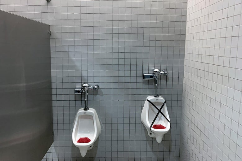 Two urinals, one taped off for social distancing.