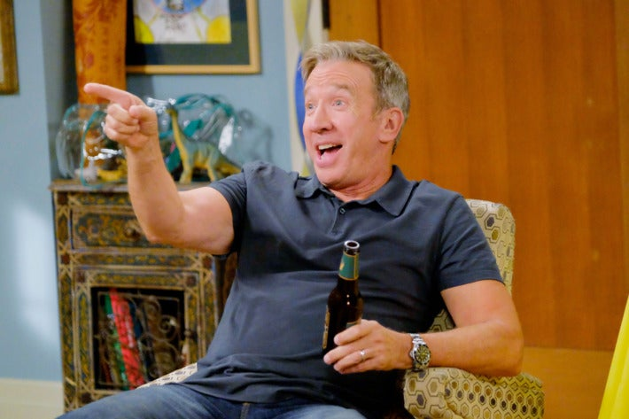 Actor Tim Allen on the TV show Last Man Standing. He sits in an armchair, a beer in his right hand while he enthusiastically points with his left. He has a happy expression on his face. He wears a navy blue polo shirt and jeans.