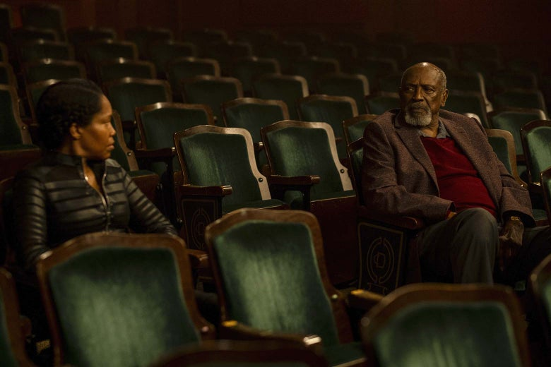 Regina King and Louis Gossett Jr. stare at each other across auditorium seating in this still from Watchmen.