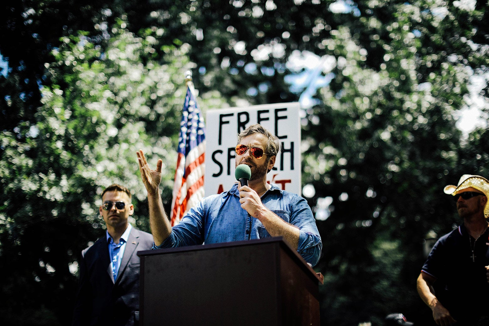 "Mike Cernovich speaks during a rally with a sign that says ""Free Speech"" in the background."