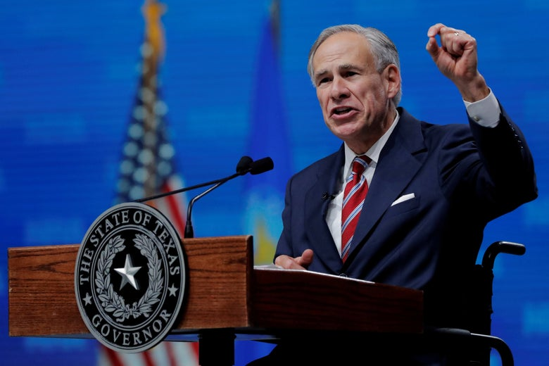 Greg Abbott gestures while speaking at a podium at a convention with an American flag in the background.