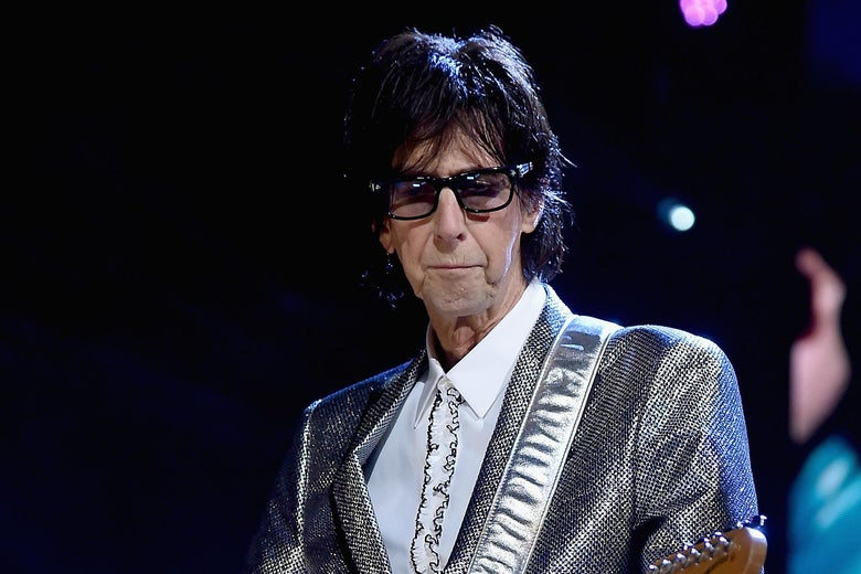 Ric Ocasek playing a guitar on stage.