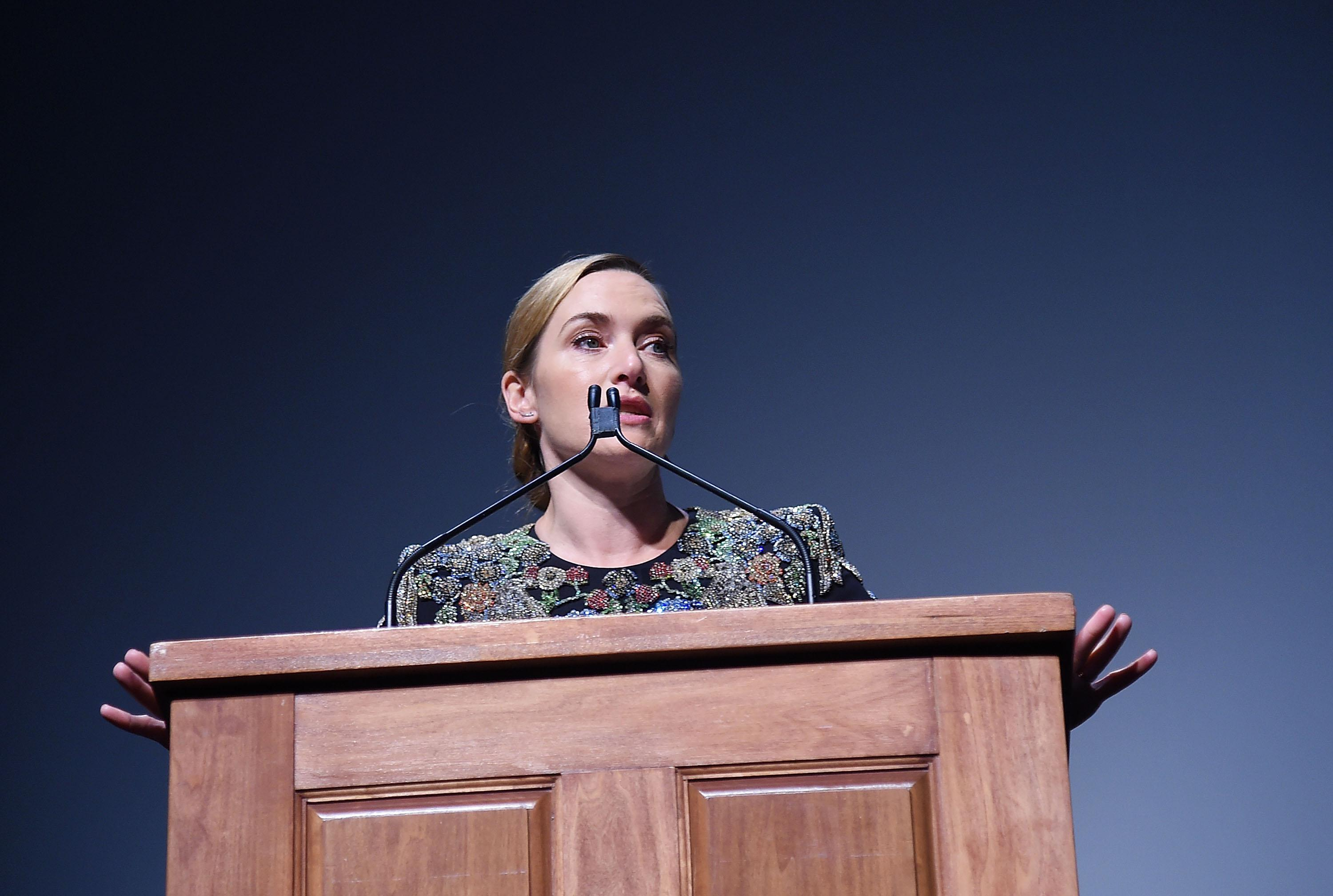 Kate Winslet stands at a podium