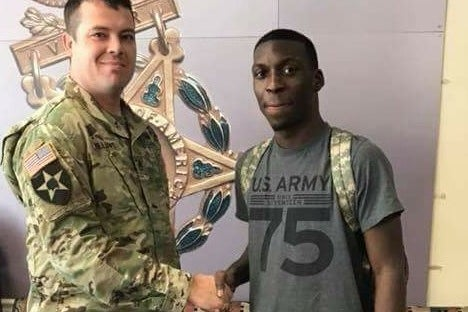 Bradford in an army tee shirt smiles and shakes hands with a man in an army uniform.