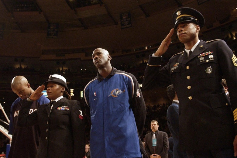 Michael Jordan stands between two members of the military during the national anthem.