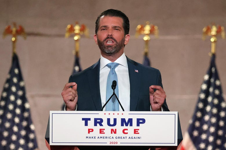 "Donald Trump Jr. stands behind a podium with a ""Trump Pence"" sign on it. He gestures with both hands, touching his pointer fingers and thumbs together. Several U.S. flags stand on poles behind him."