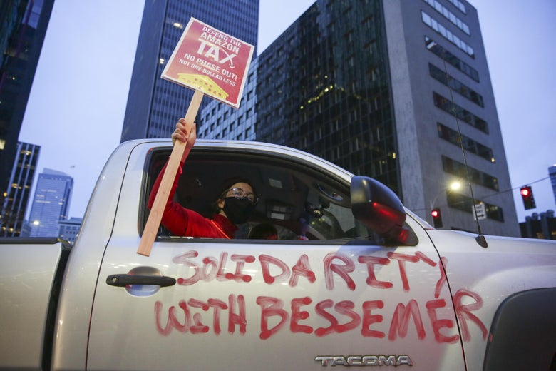 """A demonstrator holds up a """"Defend the Amazon Tax"""" sign through the passenger side window of a truck with """"Solidarity With Bessemer"""" painted on the outside, part of a Tax Amazon car caravan."""