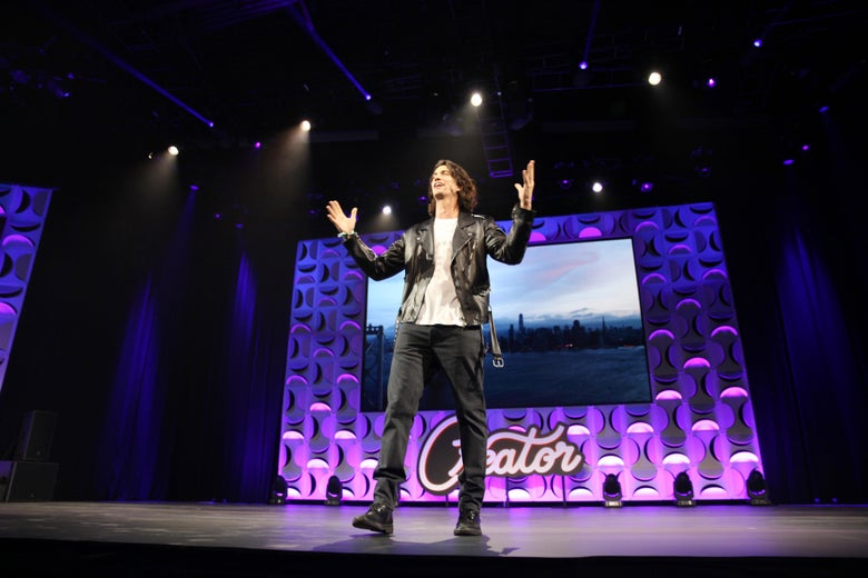 Adam Neumann is on stage wearing a leather jacket and sneakers