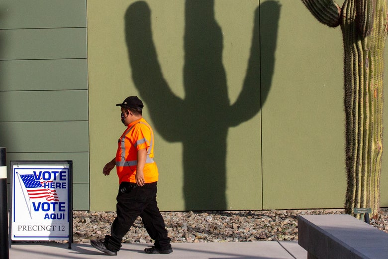 A man walks into a polling center with the shadow of a cactus visible on the wall of the building.