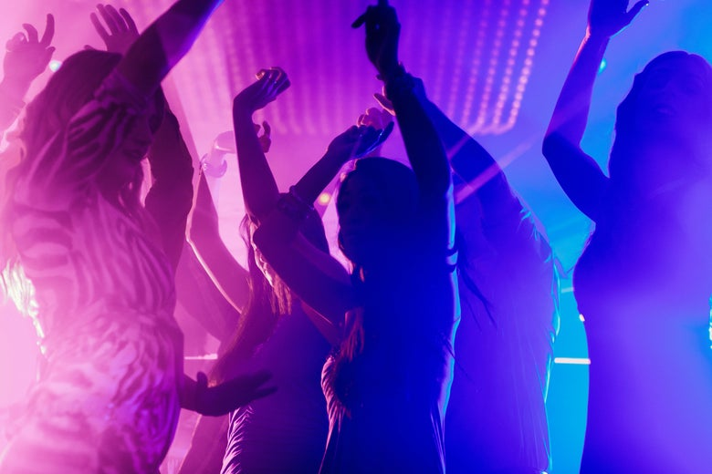 Party people at a club with bright pink and blue lights.