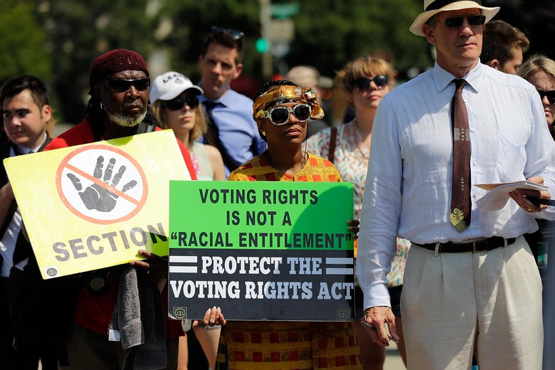 A crowd of protesters gathers with signs in support of the Voting Rights Act