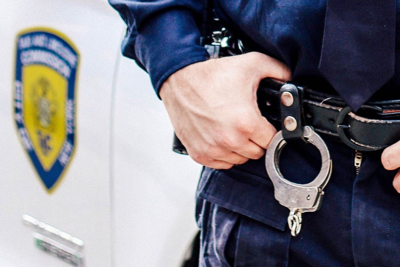 A police officer gripping his duty belt, which has handcuffs hanging off of it