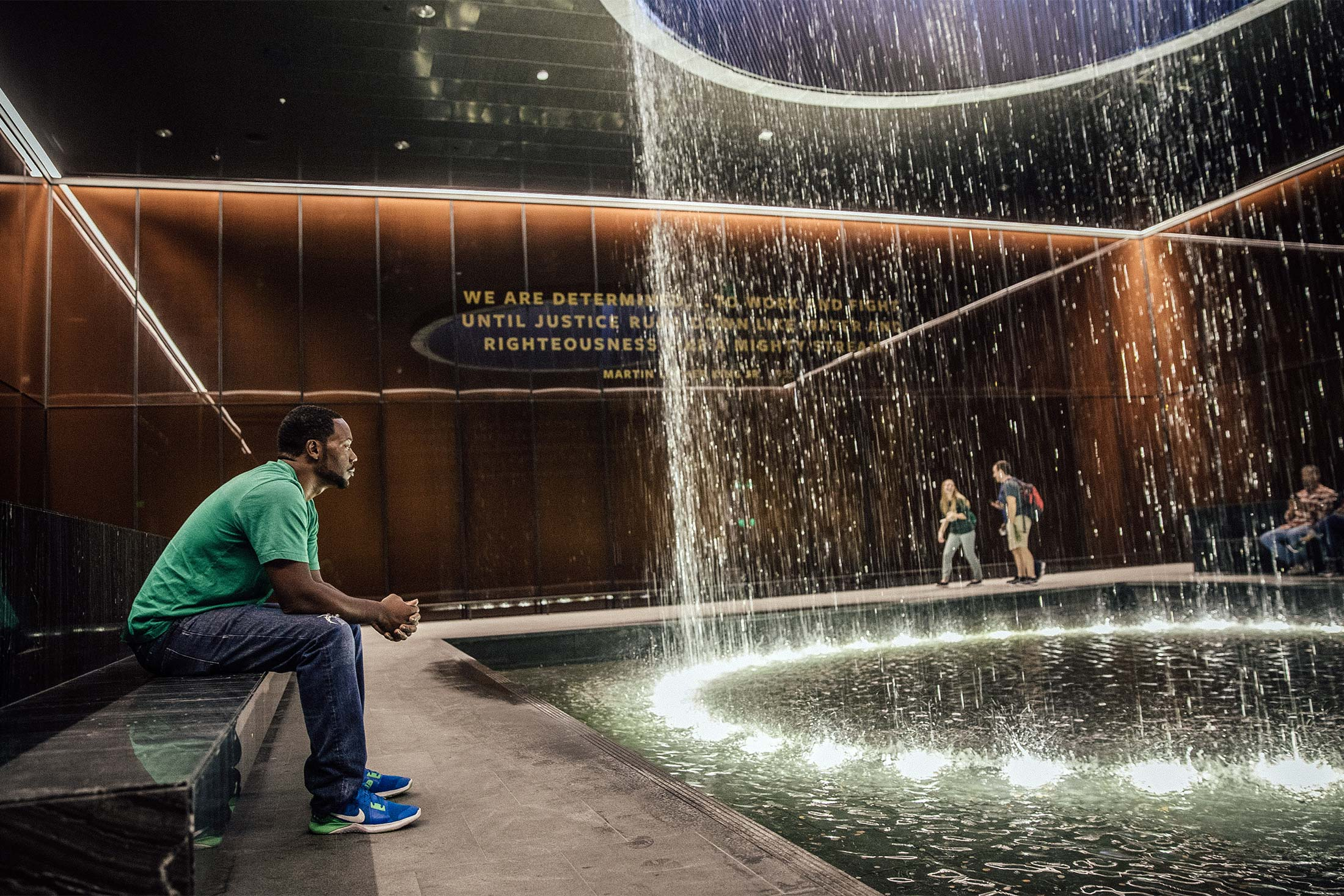 A black man sits on a bench and looks into a fountain in the National Museum of African American History and Culture.