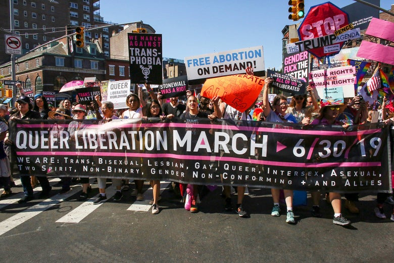 "A crowd of protesters on a street carry signs and display a banner reading ""Queer Liberation March."""