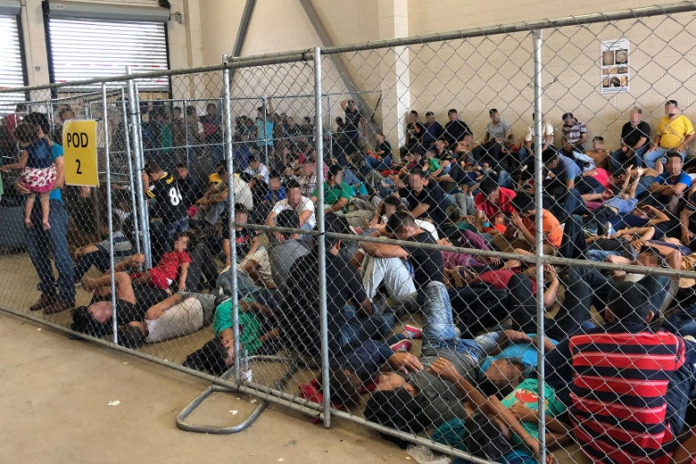 Parents and children sitting on the floor, crowded into a cage inside the detention facility.