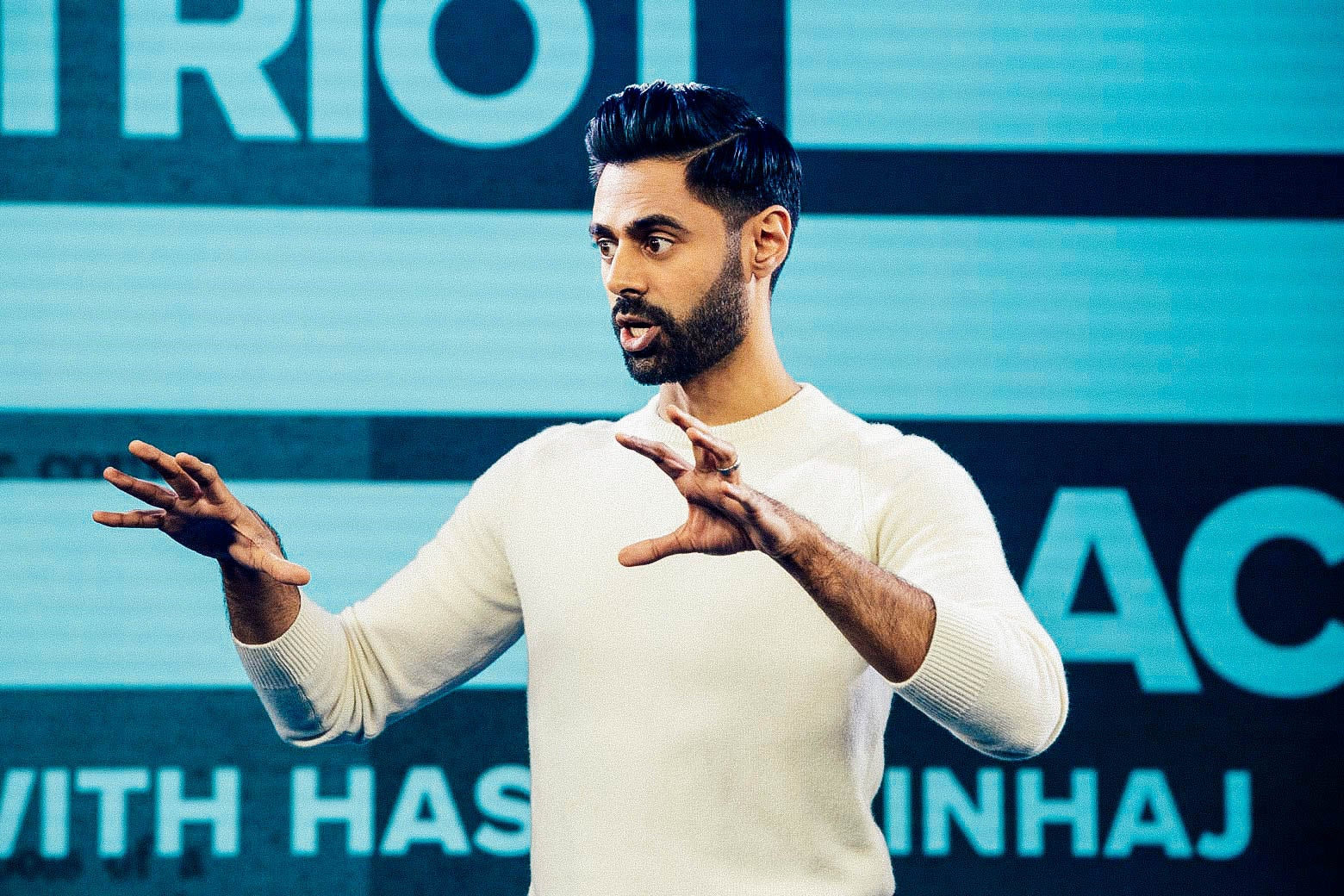 Hasan Minhaj standing with his arms raised on the stage of his show, Patriot Act.