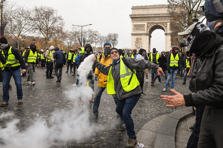 A demonstrator throws a tear gas canister during the demonstration of the yellow vests near the Arc de Triomphe on December 8, 2018 in Paris France.