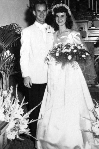 Irene holding a bouquet and standing beside her husband, both in wedding attire.