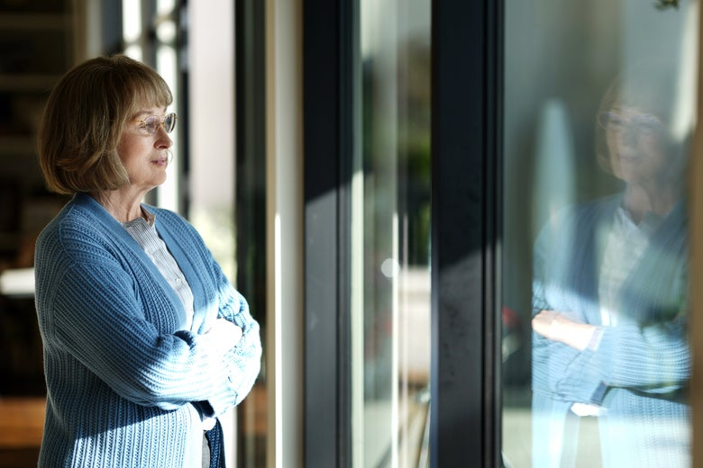 Meryl Streep, with arms crossed, looks out a window.