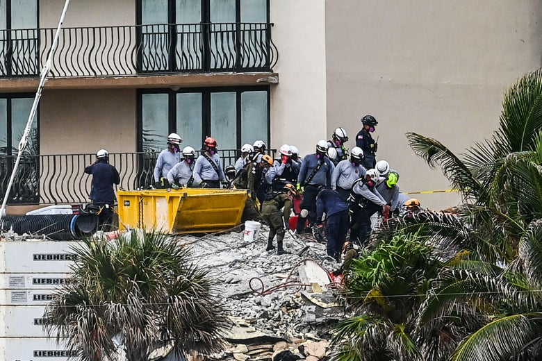 About a dozen people wearing hard hats stand on rubble of a condo building.