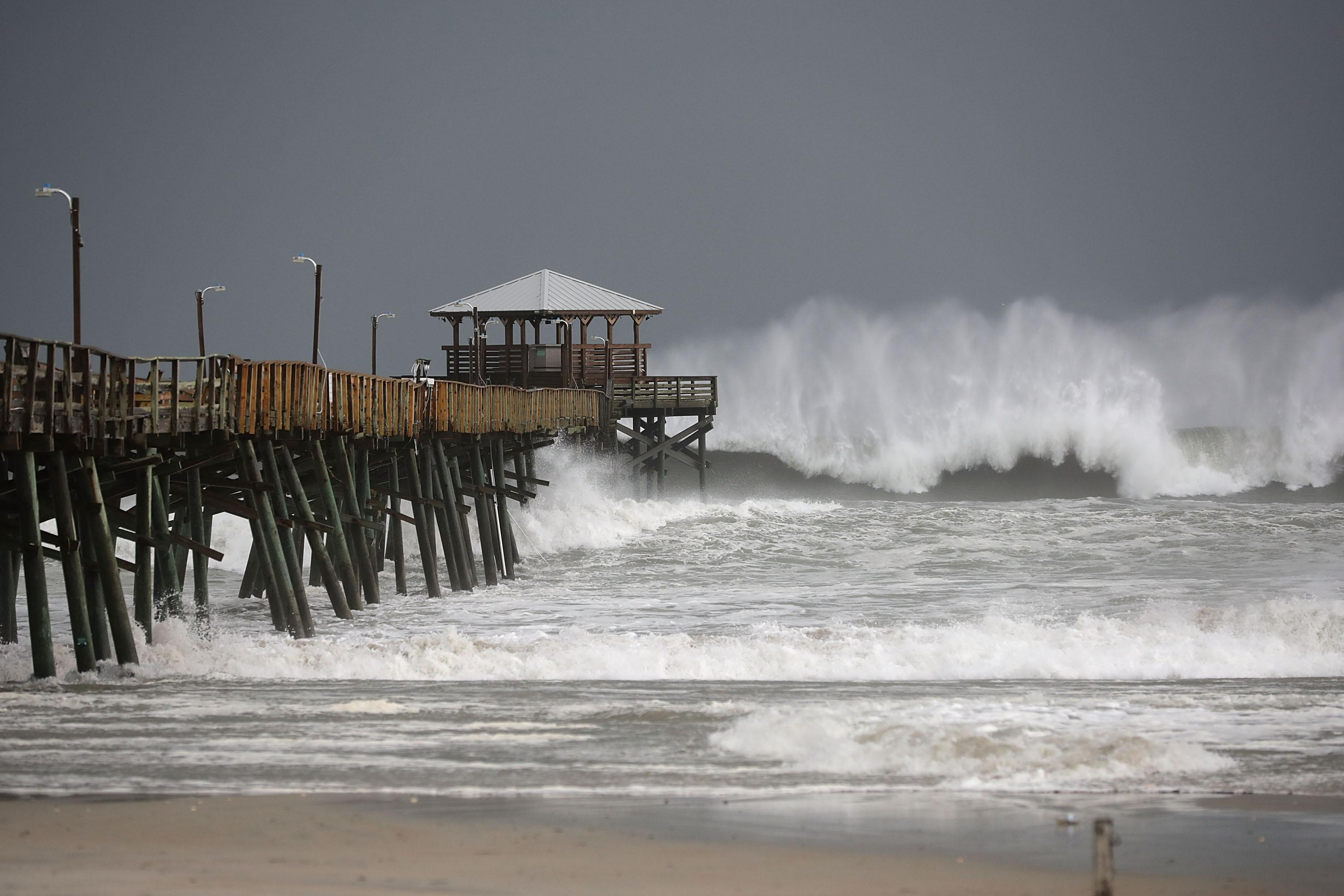High waves crash around a pier in front of a gray, stormy sky.