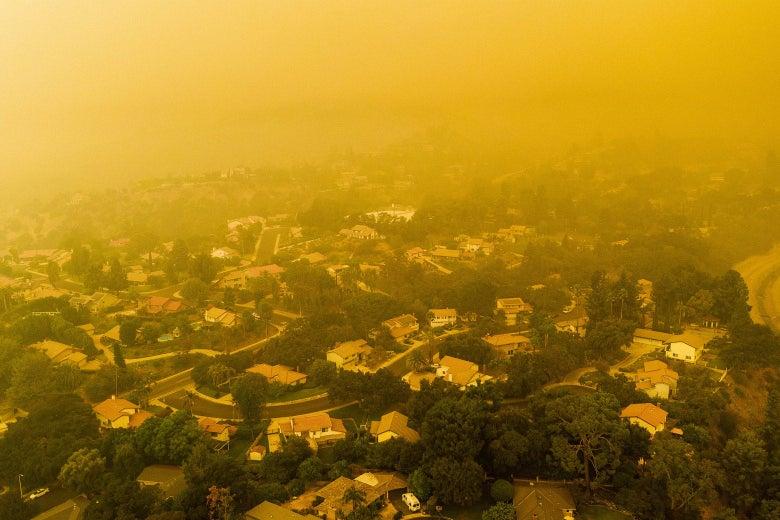 An aerial view of houses in a neighborhood beneath a cloud of orange smoke.