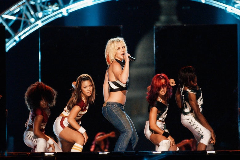 Britney Spears performing onstage with backup dancers behind her.