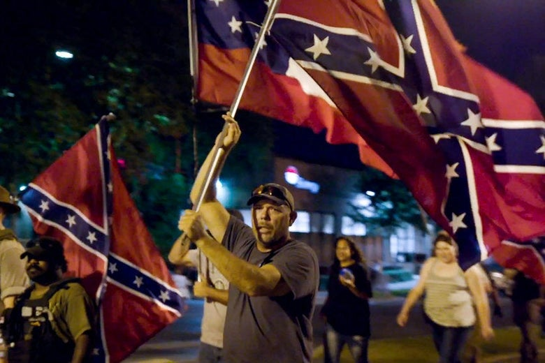 A man holds a large Confederate battle flag as he marches down a street at night. Several people march with him, one also holding a Confederate flag.