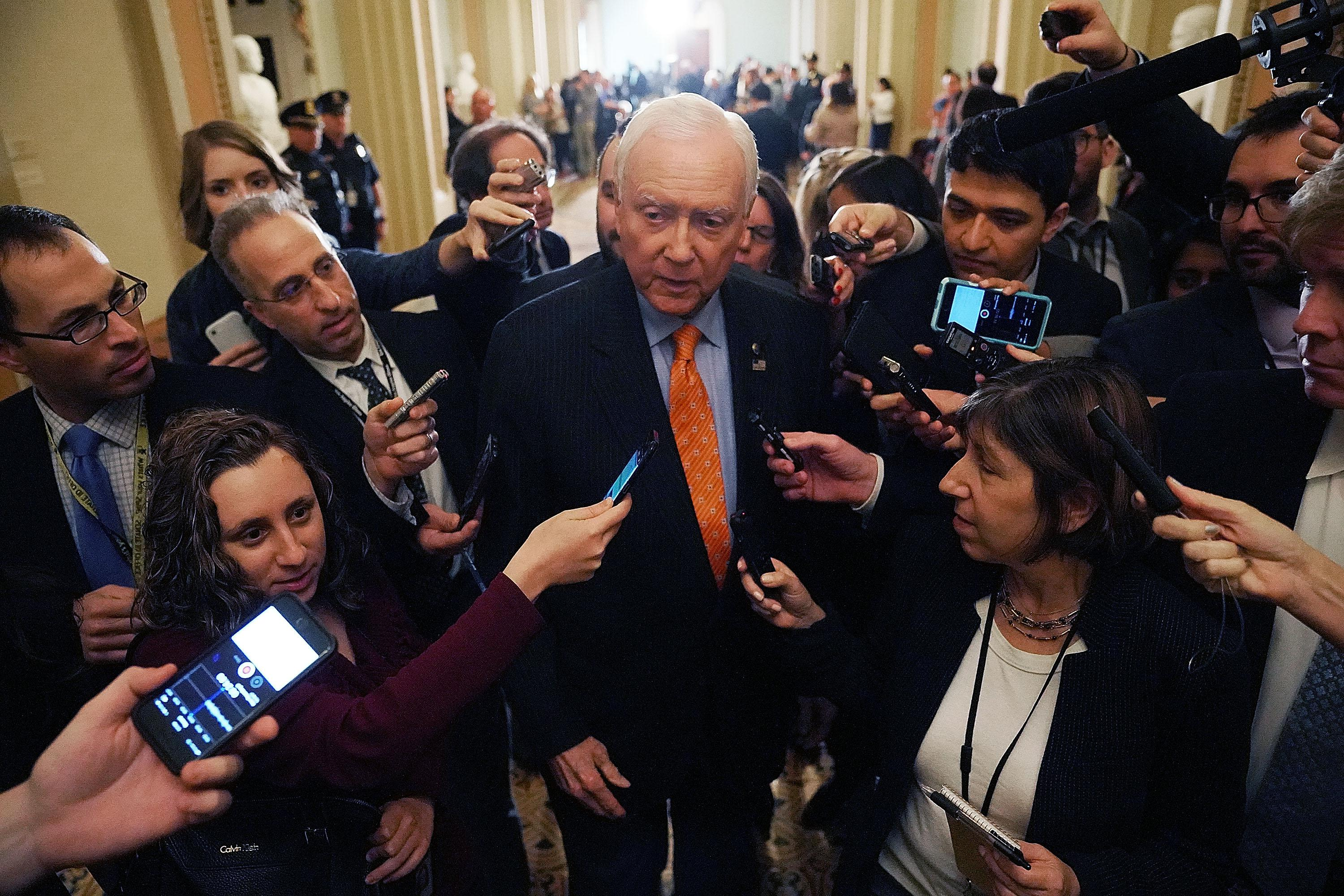 WASHINGTON, DC - NOVEMBER 14:  Senate Finance Committee Chairman Orrin Hatch (R-UT) (C) is surrounded by reporters as he leaves the weekly Senate Republican policy luncheon in the U.S. Capitol November 14, 2017 in Washington, DC. Senate Republicans are considering including a repeal of the Obamacare individual mandate as part of their proposed tax cut and reform legislation, which they want to pass the week after the Thanksgiving holiday.  (Photo by Chip Somodevilla/Getty Images)