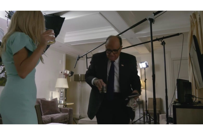 A still from Borat showing Tutar in a turquoise dress and Rudy Giuliani in a suit, holding glasses of whiskey, with lighting rigs around them in the room