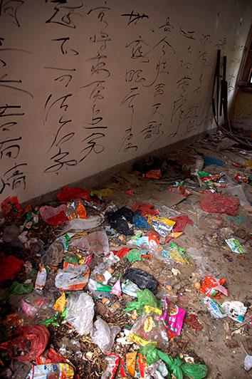 Grafitti lines the walls of an abandoned student compound in Beijing University that became an improvised garbage dump, in the student neighborhood of Wudaokou of Beijing, May 8, 2008.