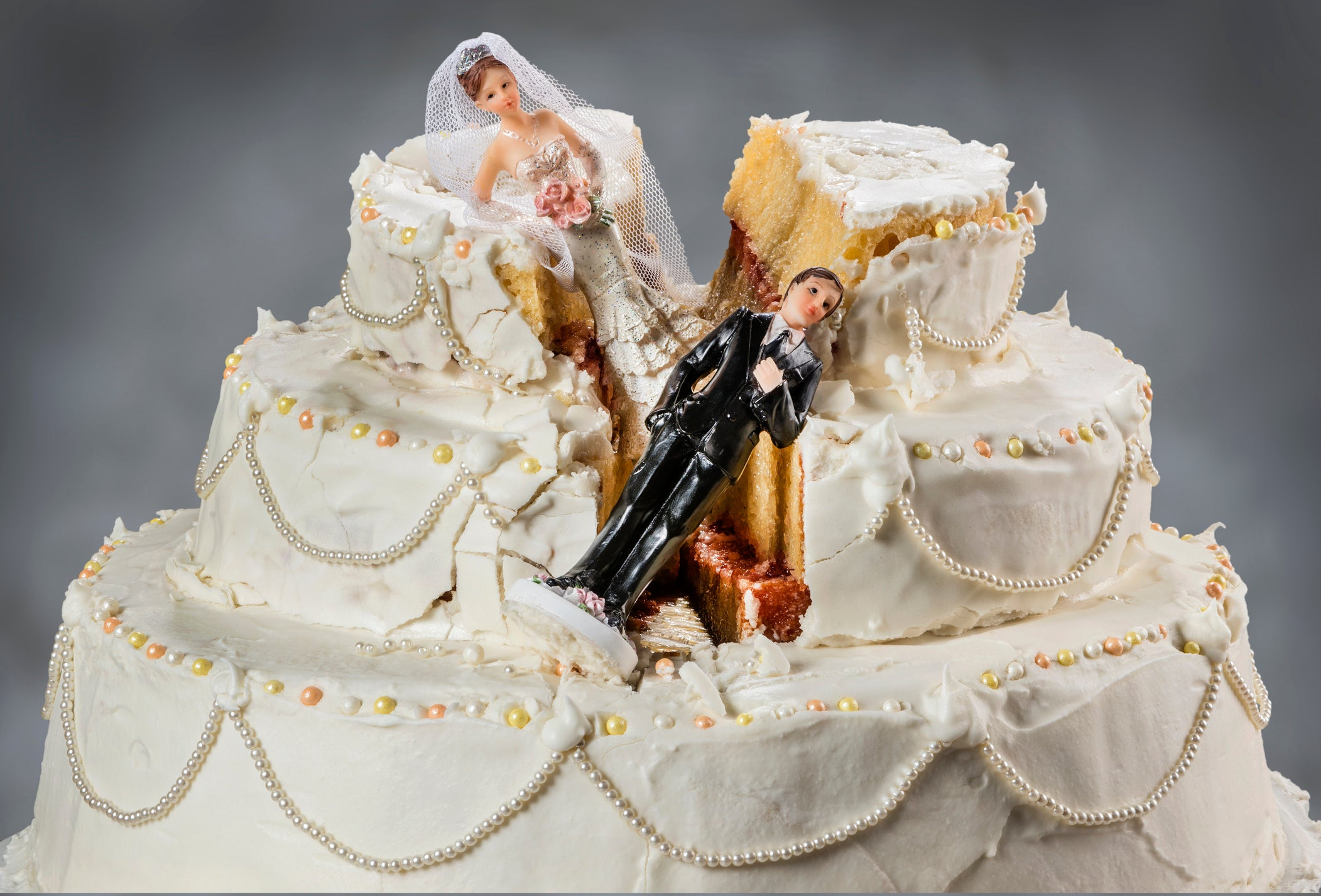 Bridge and groom figurines sink into a cut-up wedding cake.