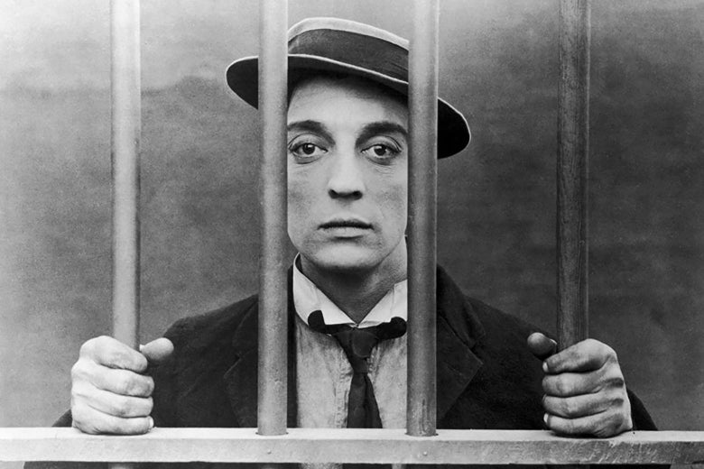 Buster Keaton, wearing his trademark pork pie hat, looks sadly out from behind bars.