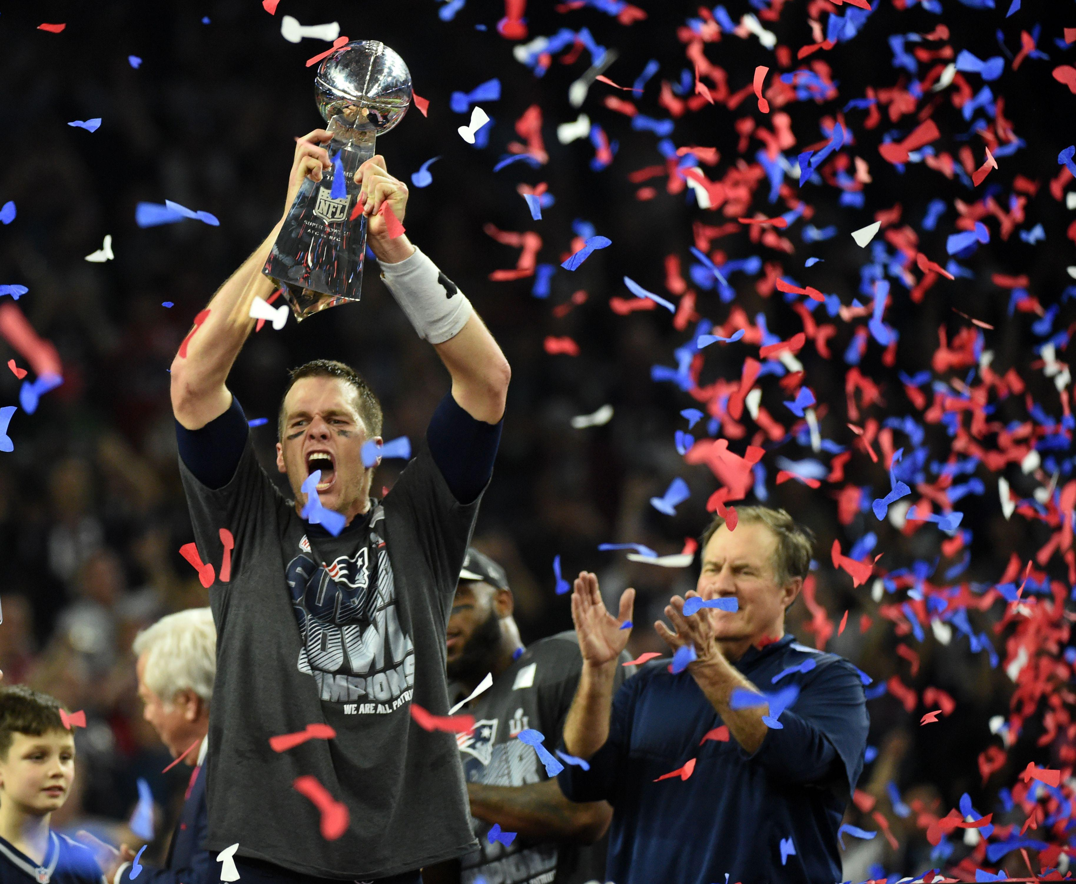 Tom Brady #12 of the New England Patriots holds the Vince Lombardi Trophy as Head coach Bill Belichick (R) looks on  after defeating the Atlanta Falcons 34-28 in overtime during Super Bowl 51 at NRG Stadium on February 5, 2017 in Houston, Texas.         The Patriots defeated the Falcons 34-28 after overtime.  / AFP / Timothy A. CLARY        (Photo credit should read TIMOTHY A. CLARY/AFP/Getty Images)