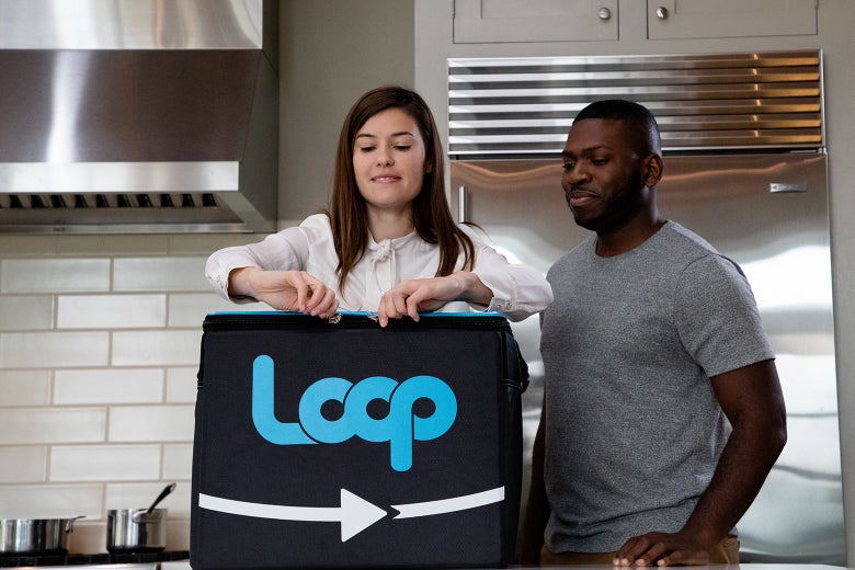 Image of two people standing next to a large reusable Loop brand container.