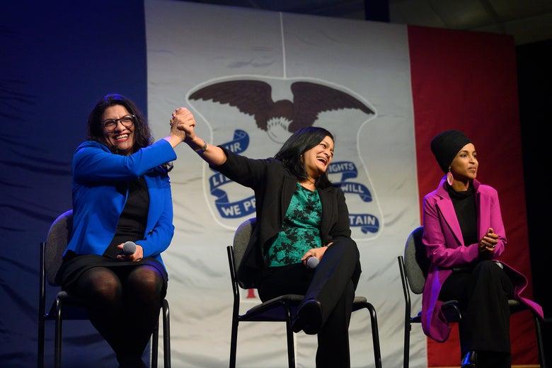 Congresswoman Rashida Tlaib (L), D-MI, high-fives US Congresswoman Pramila Jayapal (C), D-WA, with US Congresswoman Ilhan Omar, D-MN, as they speak to supporters of Democratic presidential candidate Senator Bernie Sanders at a campaign event in Clive, Iowa, on January 31, 2020.
