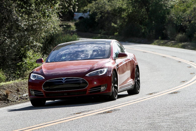 Red Tesla driving on a highway