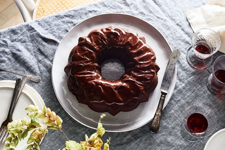 A beautiful chocolate bundt cake, covered in chocolate ganache, sits in the center of a table with glasses of Passover wine.