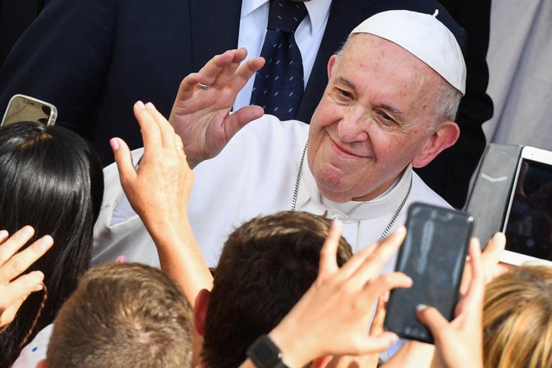 Pope Francis waves as a crowd of people reach for him and take photos.